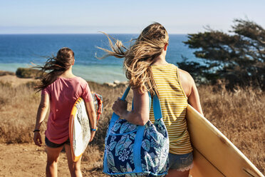 Two women carrying surfboards at the coast - WESTF22015