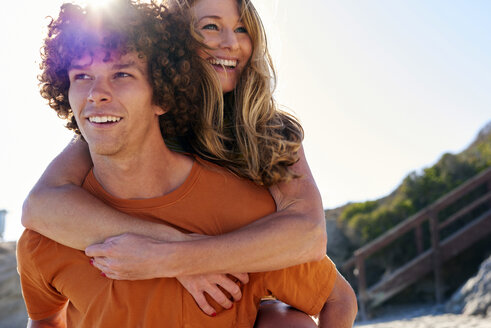 Happy young man carrying girlfriend piggyback on the beach - WESTF22024