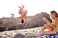 Young man on the beach doing a somersault with woman checking cell phone - WESTF22030