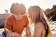 Couple checking cell phone on the beach - WESTF22033