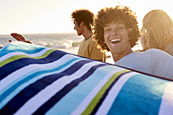 Happy young man with towel on the beach - WESTF22057
