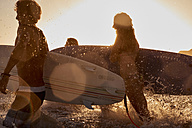 Surfers in the sea at sunset - WESTF22066