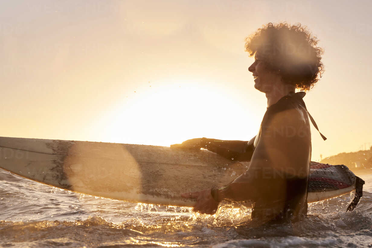 Happy surfer in the sea at sunset - WESTF22069 - Fotoagentur WESTEND61/Westend61
