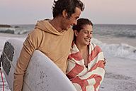 Smiling young couple on the beach carrying surfboard - WESTF22075