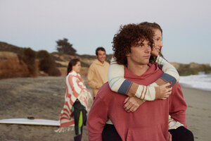 Young man carrying girlfriend piggyback on the beach - WESTF22078