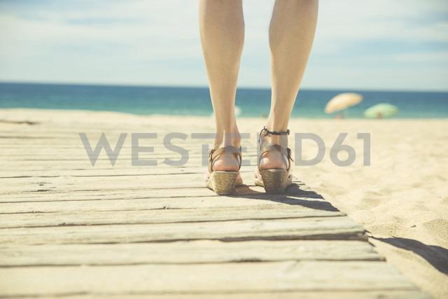 Legs of woman standing at boardwalk on the beach - CHPF00351