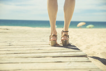 Legs of woman standing at boardwalk on the beach - CHPF00351