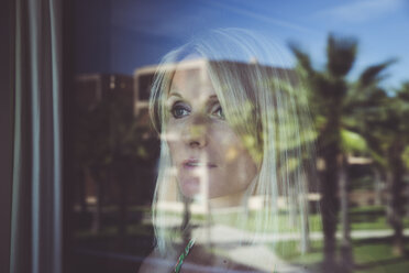Woman looking out of window with reflecting palm trees - CHPF00354