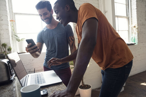 Two smiling young men with cell phone and laptop in a loft - WESTF22080