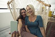 Two happy young women in hammock taking a selfie - WESTF22113
