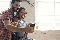 Playful young couple taking a selfie in a loft - WESTF22116