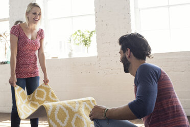 Young couple placing carpet in a loft - WESTF22119