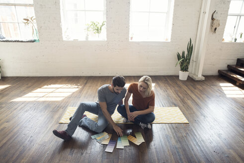 Young couple sitting on carpet in a loft looking at color samples - WESTF22125