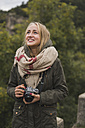 Smiling young woman with camera outdoors - KKAF00074