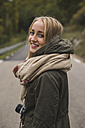 Portrait of smiling young woman with camera outdoors - KKAF00077