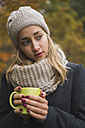 Young woman with hot beverage in autumn - KKAF00080