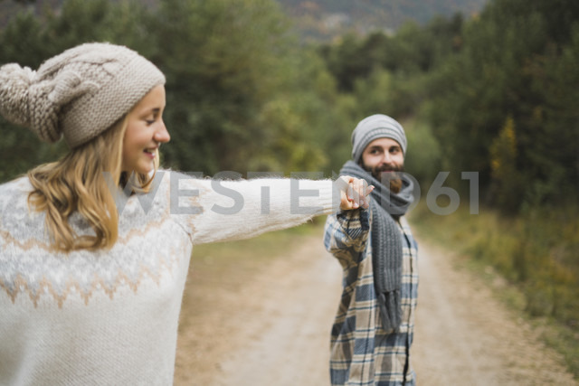 Young couple hand in hand on path in autumn - KKAF00095