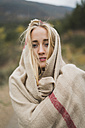 Portrait of young woman wrapped in a blanket outdoors - KKAF00098