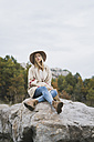 Young woman wearing hat sitting on boulder - KKAF00101