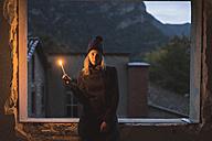Young woman shining a light at dusk - KKAF00104