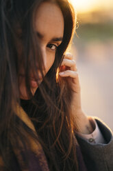 Portrait of woman with brown hair at sunset - KKAF00143