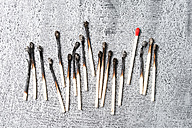 Red match between burned matches - MYF01855