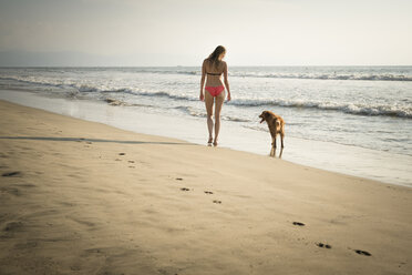 Mexico, Riviera Nayarit, Woman walking with dog at the beach - ABAF02099