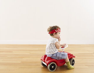 Little girl playing with pedal car - FSF00625