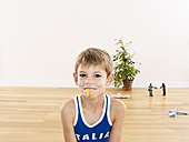 Portrait of little boy holding French fries with his mouth - FSF00631