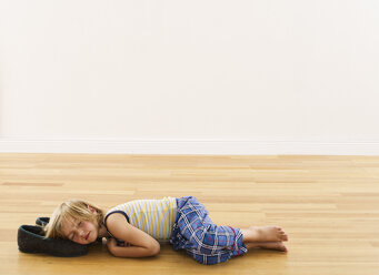 Little boy lying on wooden floor with head on slippers - FSF00634