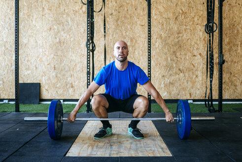 Man ready to lift barbell in gym - KIJF00916