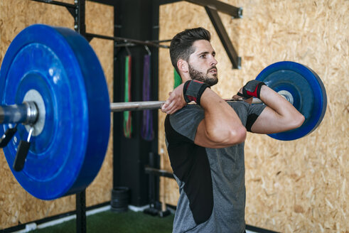 Man lifting barbell in gym - KIJF00922