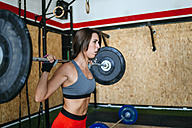 Woman lifting barbell in gym - KIJF00925