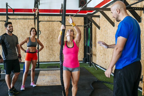 Group of athletes watching woman climbing a rope in gym - KIJF00928