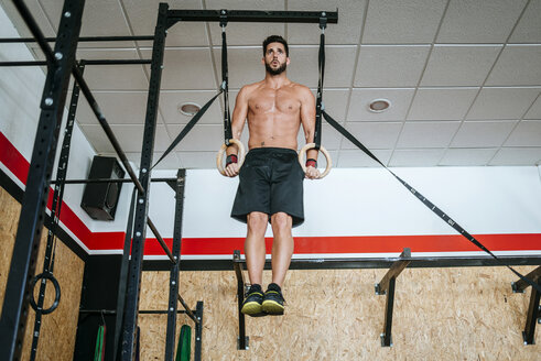 Man doing exercises on rings in gym - KIJF00937