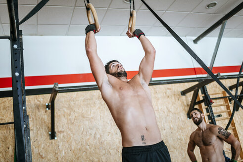 Man doing exercises on rings in gym - KIJF00940