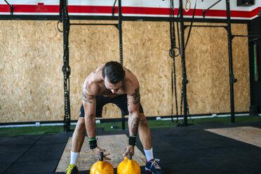 Man preparing to lift kettlebells in gym - KIJF00943
