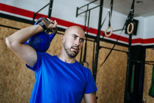 Man lifting kettlebell in gym - KIJF00946