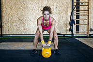 Woman preparing to lift kettlebell in gym - KIJF00949