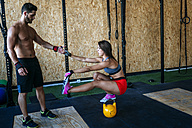 Man helping woman keeping balance on a kettlebell in gym - KIJF00952