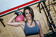 Portrait of smiling woman holding kettlebell in gym - KIJF00955