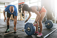 Man and woman preparing barbell in gym - KIJF00958