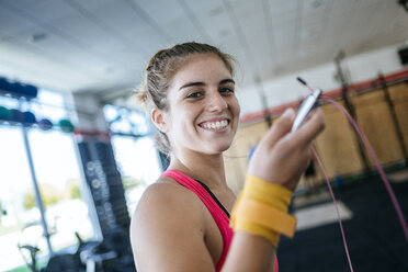 Portrait of smiling woman holding skipping rope in gym - KIJF00964