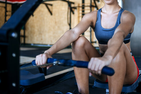 Close-up of woman exercising with a rowing machine in gym - KIJF00967