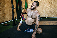 Man doing stretching exercises in gym - KIJF00976