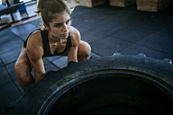 Woman exercising with a tractor tyre in gym - KIJF00979