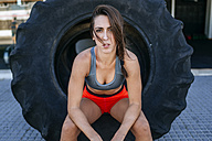 Female athlete sitting in tractor tyre - KIJF00985