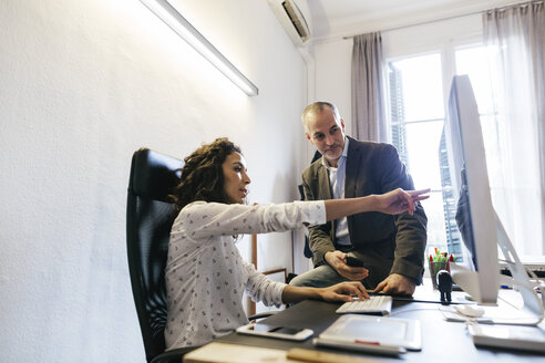 Businessman and woman in office working together on computer - EBSF01880