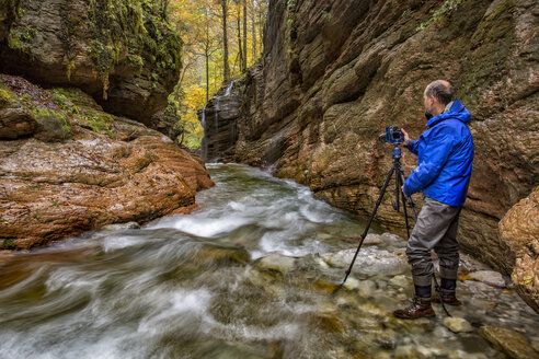 Austria, Tennegau, Photographer standing at Taugl river - YRF00144