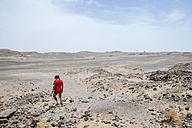 Morocco, Merzouga, woman walking through the stone desert - KIJF00996